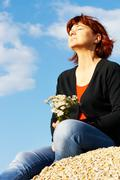 portrait of middle aged female with bunch of flowers enjoying warm day - stock photo