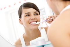 Image of pretty female brudhing her teeth in front of mirror in the morning Stock Photos