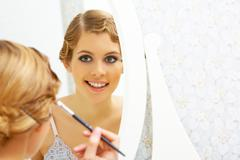 Image of pretty female looking in mirror and doing makeup Stock Photos