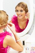 Image of pretty female looking in mirror and putting on earrings Stock Photos