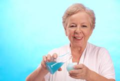 portrait of aged woman with flusk and cream looking at camera - stock photo