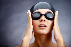 Portrait of a young woman in goggles and swimming cap Stock Photos