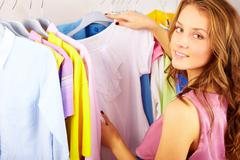 A girl choosing t-shirt in the shop Stock Photos