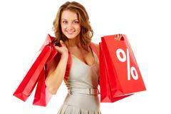 Portrait of a girl holding handbags with discount symbol, looking at camera and Stock Photos