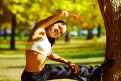 a young girl making bodily exercises in autumn park - stock photo