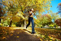 a young girl running in autumn park - stock photo