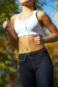 close-up of a young woman jogging with a player - stock photo