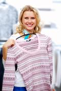 Portrait of pretty woman choosing new sweater and looking at camera in clothing Stock Photos