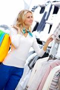 portrait of pretty woman choosing new sweater in clothing department - stock photo