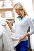 Portrait of pretty woman choosing new winter coat in clothing department Stock Photos