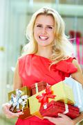 Portrait of pretty woman with giftboxes after good shopping Stock Photos
