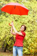 portrait of beautiful woman holding red umbrella - stock photo