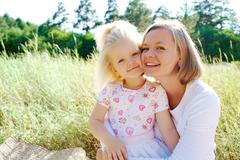 portrait of mother embracing her daughter during summer vacation - stock photo