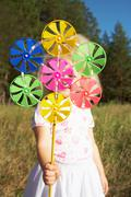 portrait of cute girl behind pinwheel toy held by her - stock photo