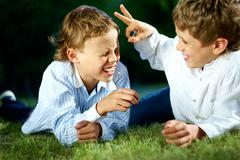 portrait of happy boys playing jokes on grass in park - stock photo