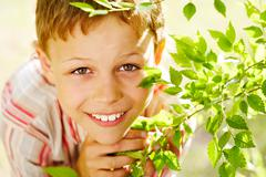Portrait of handsome schoolboy smiling at camera out of green branch Stock Photos