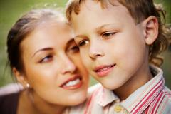 Close-up of a boy's face and his mother looking at him in the background Stock Photos
