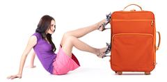 image of young woman pushing her orange suitcase - stock photo