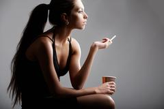 Portrait of pretty female smoking with plastic glass in hand Stock Photos