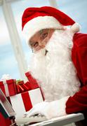 Portrait of santa claus typing and looking at camera Stock Photos