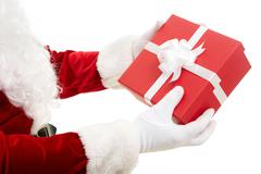 close-up of santa claus hands holding red giftbox - stock photo