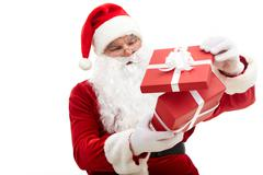 Photo of happy santa claus looking into red giftbox in isolation Stock Photos