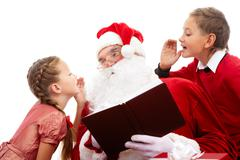 Image of santa listening to little boy and girl whispering their wishes for chri Stock Photos