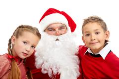 image of happy santa between little boy and girl looking at camera - stock photo