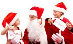 image of santa between little boy and girl giving him christmas letters - stock photo
