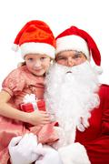 image of happy santa holding little girl with gift and both looking at camera - stock photo