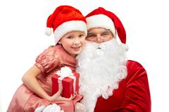 Image of happy santa holding little girl with gift and both looking at camera Stock Photos