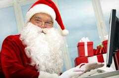 portrait of santa claus in front of computer monitor looking at camera - stock photo