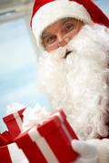photo of happy santa claus with red giftbox looking at camera - stock photo