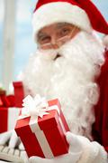 photo of santa claus hand holding red giftbox - stock photo