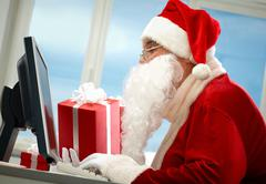 portrait of santa claus in front of computer monitor with gifts - stock photo
