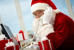 Photo of busy santa claus communicating by telephone Stock Photos