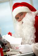 santa holding christmas letter and looking at camera - stock photo