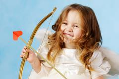 Cute female cupid holding bow Stock Photos
