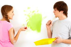 young happy girl painting wall in new house and looking at pensive guy - stock photo