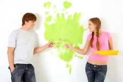 affectionate couple holding paintbrushes while looking at each other with painte - stock photo