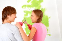 Cheerful couple touching by paintbrushes while looking at each other with painte Stock Photos