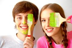 Stock Photo of image of joyful couple hiding one of eyes behind paintbrushes with green color