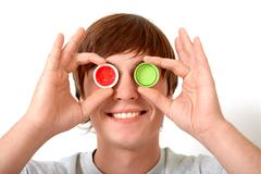 Image of smiling guy hiding eyes behind plastic corks with green and red paint Stock Photos