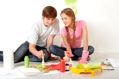 Photo of young couple mixing paints during flat improvement Stock Photos