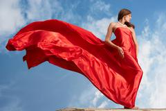 photo of graceful female folded in bright red silk shawl with cloudy sky at back - stock photo