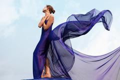 Photo of graceful female folded in dark blue chiffon shawl with cloudy sky at ba Stock Photos
