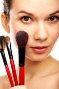 Close-up of young gorgeous female with brushes looking at camera Stock Photos