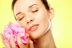 gorgeous woman with pink flower over yellow background - stock photo