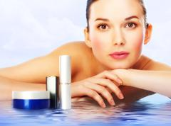 Beautiful woman with professional makeup lying on water surface with cosmetic pr Stock Photos
