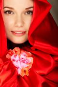 Stock Photo of gorgeous woman in red satin holds flower looking at camera